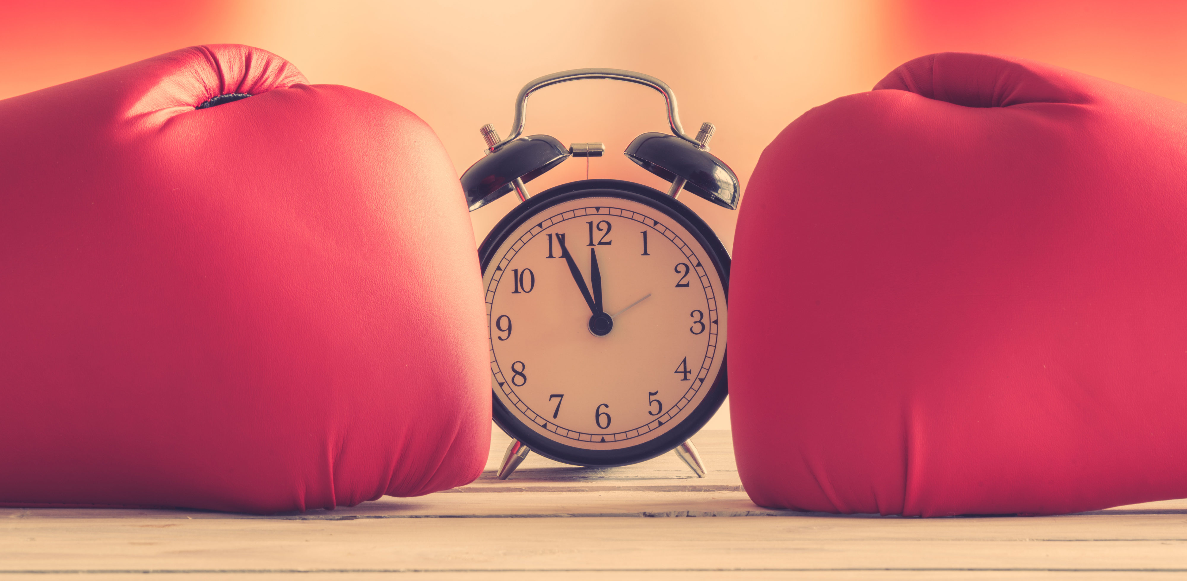 Boxing gloves punching a classic alarm clock showing time