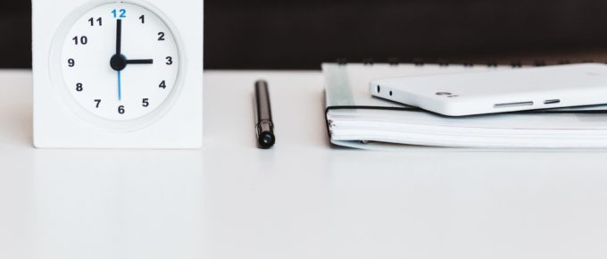 A clock, pen, notebook, and smart phone on a white desk.